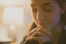 A young woman with hands folded in prayer
