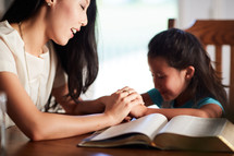 mother and daughter reading the Bible and praying together at the kitchen table