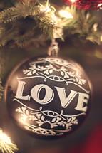 love Christmas ornament on a Christmas tree