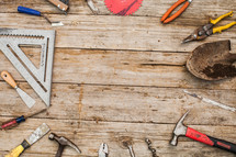 Tools laid in a circle on a rustic wooden table.