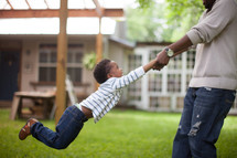 father swinging his son outdoors