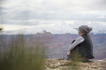a woman sitting on a mountaintop looking out