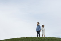 sisters standing on a hilltop holding hands