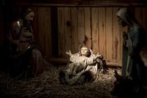 Mary and Joseph gazing upon baby Jesus in manger in nativity scene.