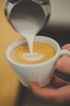 pouring cream in coffee