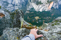 looked down from a cliff in rugged mountains and evergreen forest