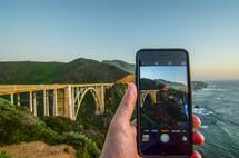 taking a picture of a bridge along a shoreline