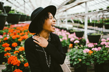 An African American woman in a black hat standing in a green house full of flowers