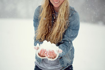 a young woman with a hand full of snow