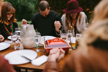Friends Praying Together Before Thanksgiving Dinner