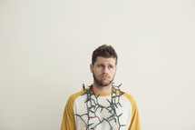 string of Christmas lights around a man's neck