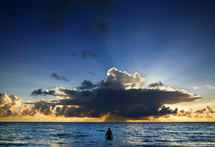 The silhouette of a person standing in the open ocean looking at God's beauty in the sun rays bursting through the clouds at sunset.