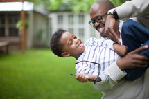A father holding and playing with his young son in the backyard.