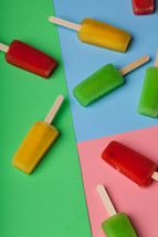 Brightly colored popsicles on a multi-colored background.