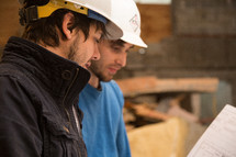 two men wearing hard hats and looking at blue prints