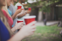 friends holding red cups at a cookout