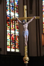 Golden catholic crucifix with stained glass cathedral windows behind