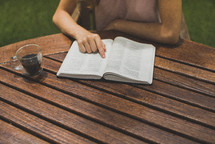 a young woman reading a Bible in her backyard