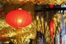 A red Chinese lunar new year lantern hanging in a gold room.