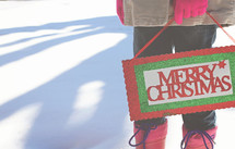 a woman in the snow holding a Merry Christmas sign