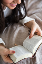 young woman reading a Bible in her bed