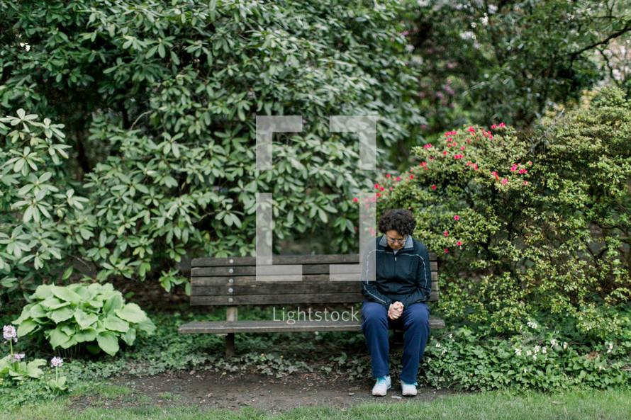 a woman sitting on a park bench praying
