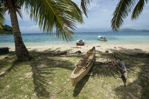 Boats on beach and kayak under the palm trees.