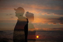 silhouettes of man and a woman at sunset