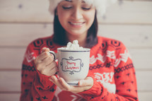 a woman in a Santa hat holding mug of hot cocoa