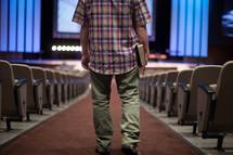 man walking down the center of a church aisle