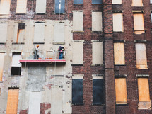 construction crew hanging from a window washer pulley system