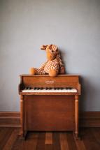 stuffed animal giraffe and a kids piano