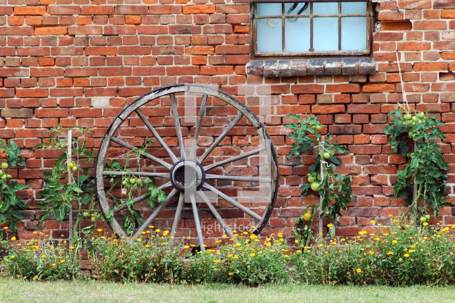 wagon wheel against a brick wall