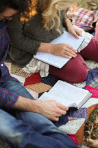 couple sitting on a blanket reading a Bible