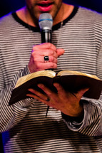 Man reading the Bible into a microphone.