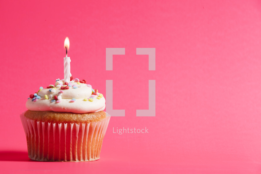 cupcake and candle against a pink background