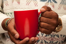 a man in a sweater holding a red coffee mug