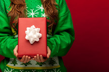 a woman in a Christmas sweater holding a wrapped gift