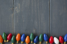 a row of colored lightbulbs on wood.