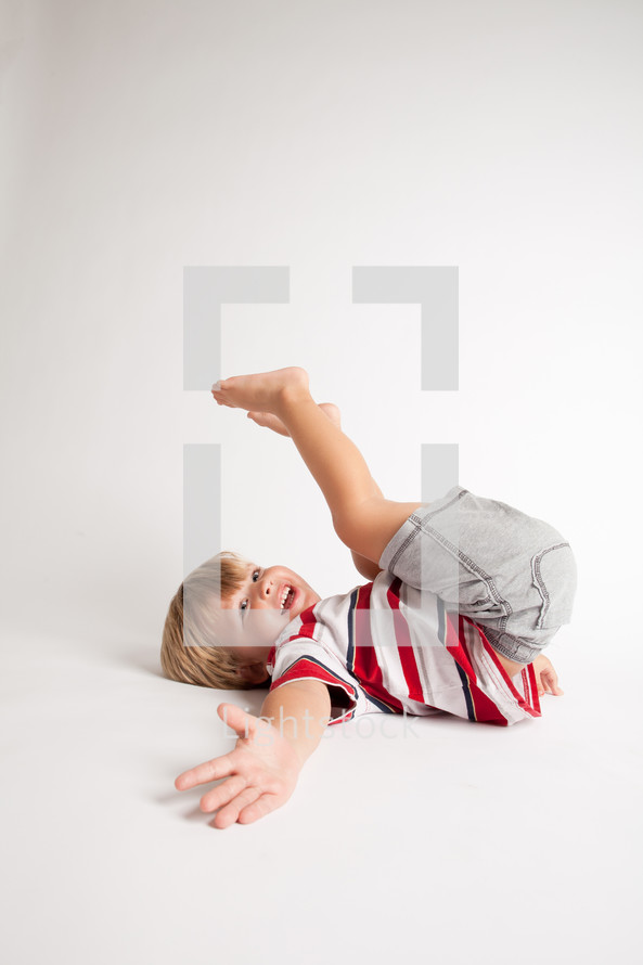 little boy playing lying on the floor
