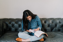 a woman sitting on a couch reading a Bible and taking notes in a journal
