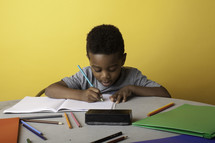 a boy coloring on paper