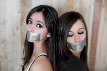 Women with their mouths duct taped.