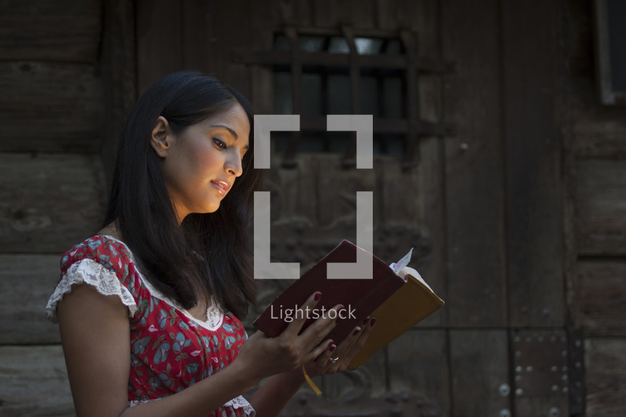 woman with face glowing reading a Bible