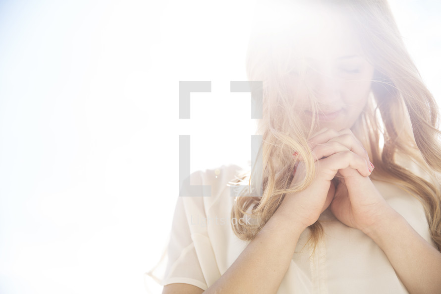 a woman with praying hands standing in intense sunlight