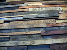 A wall of wood pieces showing different woods and wood patterns such as oak and pine to form a background of different wood grains, textures and color.