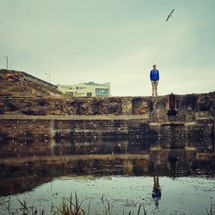 Man standing on rocks at edge of water with hill and building and flying bird in the background.