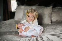 big sister holding baby sister on a bed