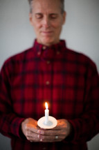 A man holding a lit candle for a candlelight service