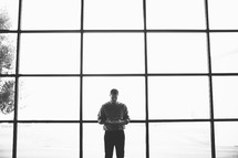 man reading a Bible standing in front of windows